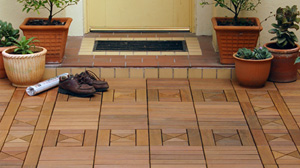 Floor made of wood deck tiles in front of a house entrance.